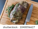 Small photo of grilled uncut roast beef on wooden cutting board and knife