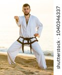 Small photo of Young guy practising aikido poses at seaside in sunset outdoor