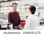 Small photo of Portrait of a handsome young man and happy customer listening to the recommendations and the advice of a reliable female pharmacist in a contemporary drugstore