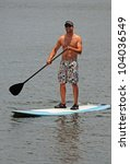 A young man in board shorts and a visor on a paddle board while exercising - stock photo