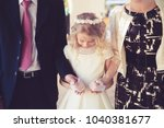 Small photo of Little Girl in her First Communion Day with Her Father and mother.