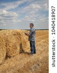 Small photo of Farmer or agronomist in wheat field after harvest examining bale, rolled straw, using tablet