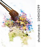Make-up brush on colorful crushed eyeshadow - stock photo
