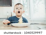 the child in the kitchen at the ... | Shutterstock . vector #1040529997