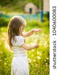Small photo of Little girl in a field with white small flowers in summer. Stellaria meadow