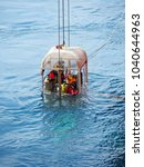 Small photo of Air divers lowered down by LARS in a cage to perform subsea work.