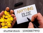 Small photo of Conceptual text showing Anything Else. Business photo showcasing Ask Asking Question to Have Answer written Notebook Book Man Writing Holding Pen wooden background