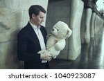 guy smiles a big plush toy.... | Shutterstock . vector #1040923087