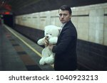 Small photo of Sad young man with a teddy bear in his hands is standing at a subway station.