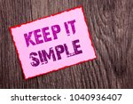 Small photo of Handwriting Announcement text showing Keep It Simple. Conceptual photo Simplicity Easy Strategy Approach Principle written Pink Sticky Note Paper the wooden background.