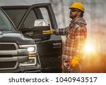 Small photo of Energy Sector Worker in the Field. Electrical Infrastructure Construction Technician and His Company Truck. High Voltage Lines Maintenance.