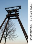 Small photo of Industry: Almost bare tree in front of the old head frame of a disused uranium mine in Eastern Thuringia