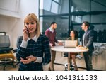 young businesswoman talking on... | Shutterstock . vector #1041311533