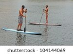 young man and woman couple paddle boarding in ocean - stock photo