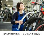 Small photo of Portrait of repairwoman standing near cycle in bicycle store