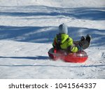 child having fun on snow tube.... | Shutterstock . vector #1041564337