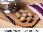 New potatoes on a chopping board with a colander, knife and tea towel - stock photo
