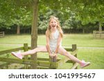 Small photo of Fun loving blonde girl straddle balancing on a fence post in the countryside, with legs split, mouth open laughing.