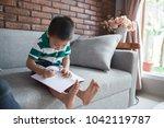 kid writing in living room... | Shutterstock . vector #1042119787