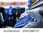 denim shirts hang on hangers in ... | Shutterstock . vector #1042188727