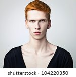 Young red haired man on light background. - stock photo