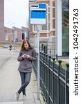 Small photo of young woman stands at a bus stop and look while waiting boredom on her phone