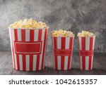 popcorn in three striped... | Shutterstock . vector #1042615357