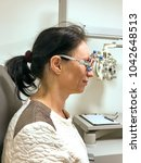 Small photo of Woman being tested for new eyeglasses at an optometrist using equipment with interchangeable corrective lenses to measure her acuity