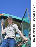 A young woman farmer stepping out of the cab of her tractor. - stock photo