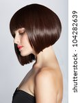 portrait of a beautiful woman in short brunette bob with neat clean hair on studio background - stock photo