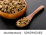 Small photo of brown sugar lump in round wooden bowl on stone plate