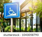 Small photo of Blue sign of wheelchair accessibility on a pole warning in front of Amazon cafe with sunlight and flare in Samutsakhon, Thailand, 10/03/2018