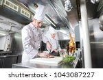 chef cutting meat on chopping... | Shutterstock . vector #1043087227