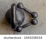 Small photo of Old rusty black kettlebell 16 kg pood and two small dumbbells on noncrete floor background top view