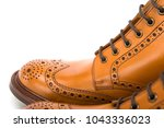 Small photo of Extreme Closeup of Mens Tanned Brogue Leather Boots with Rubber Sole. Isolated Over White Background.Horizontal Image