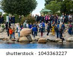 Small photo of COPENHAGEN, DENMARK - JULY 20, 2017: Unidentified people make picture of The Little Mermaid, a bronze statue by Edvard Eriksen, based on the fairy tale by Danish author Hans Christian Andersen
