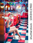 smiling young girl in retro cafe | Shutterstock . vector #1043411983