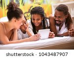 Small photo of Afro-American family with children in bedroom looking tablet screen together