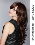 beautiful young woman with long brown curly hair in leather dress over studio background. - stock photo