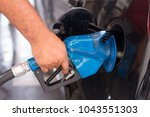 hand holding fuel pump and... | Shutterstock . vector #1043551303