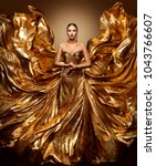 Small photo of Gold Woman Flying Dress, Fashion Model in Waving Golden Gown, Fluttering Fabric Fly like Wings, Art Beauty Portrait