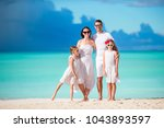 happy family on a beach during... | Shutterstock . vector #1043893597