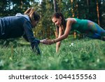 two girls doing buddy workout... | Shutterstock . vector #1044155563
