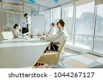 Small photo of Informative report. Pleasant young colleagues sitting at the table in the conference room and listening to the report made by their colleague standing near the whiteboard