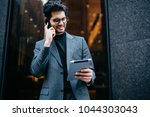 Small photo of Successful young businessman dressed in formal suit happy with advantageous business offer received on mail on digital tablet standing outdoors near office building and talking on smartphone device