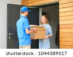 smiling delivery man in blue... | Shutterstock . vector #1044389017