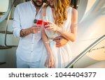 happy bride and groom drinking... | Shutterstock . vector #1044404377