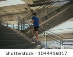 sporty man running up steps in... | Shutterstock . vector #1044416017