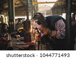 welder in protective uniform... | Shutterstock . vector #1044771493
