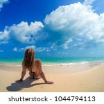 woman laying on the white sand  | Shutterstock . vector #1044794113